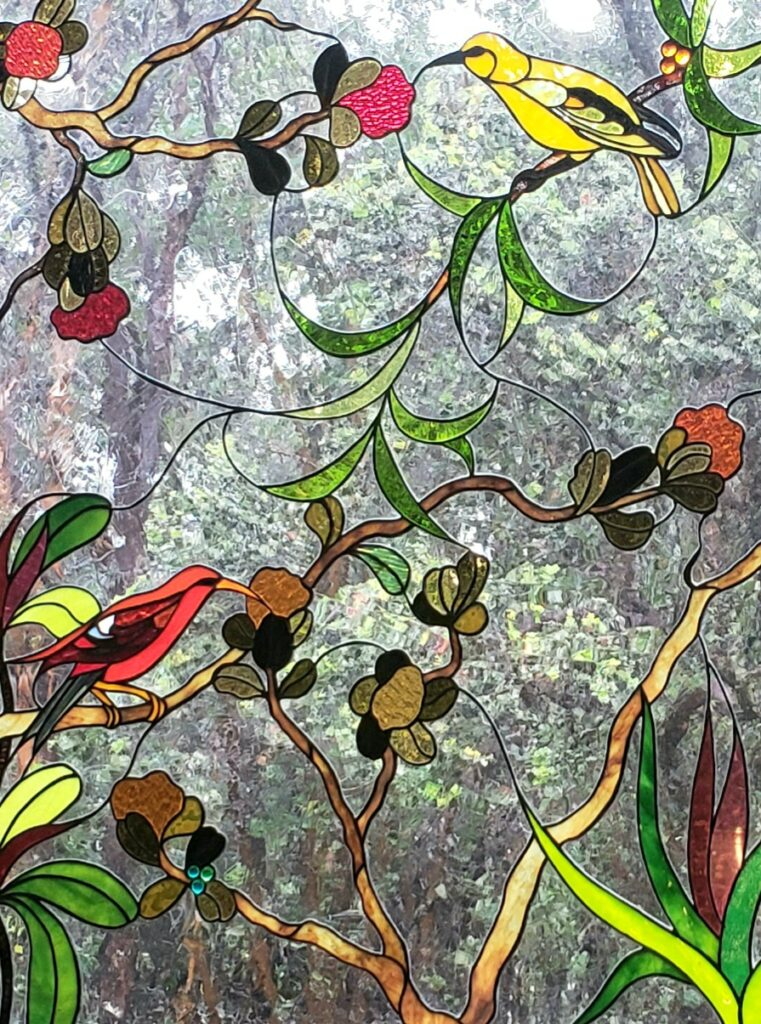 You may encounter some 'i'iwi and 'amakihi birds just like the ones depicted in the stained-glass window at Tutu's Place while wandering among the tropical flowers on the Volcano cottage grounds